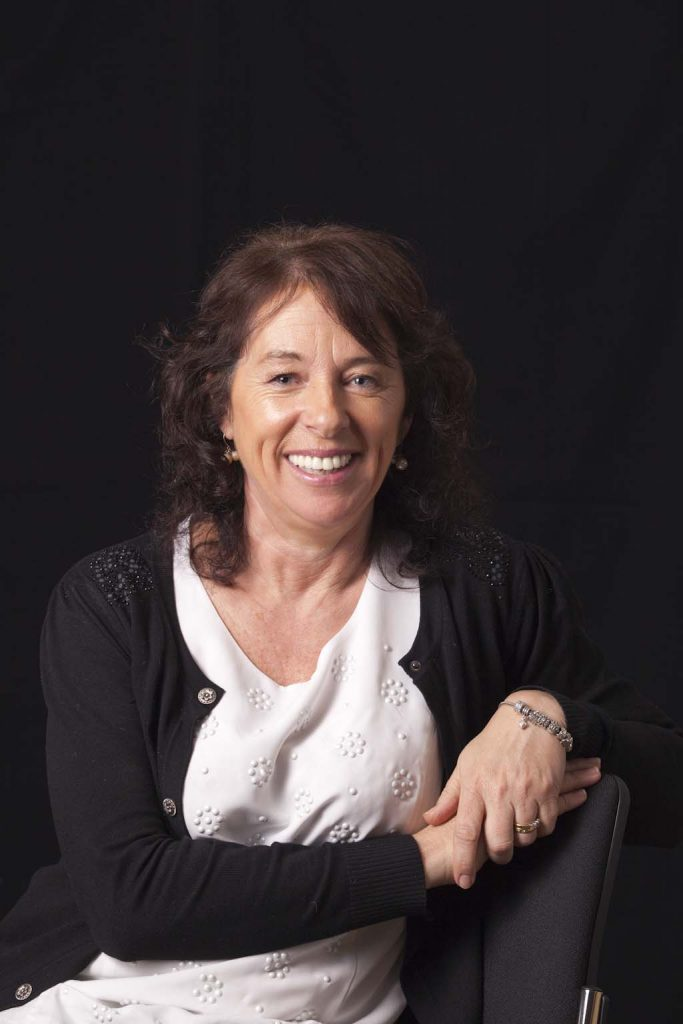 Olive O'Grady is sitting in front of a black background, wearing a white top and black cardigan. She is smiling and looking towards the camera.