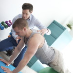 Eoin Ó Conaire chartered physiotherapist teaching a patient shoulder stability exercises