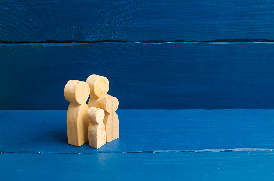 Wooden Figurines Of People In The Shape Of A Family On A Blue Ba