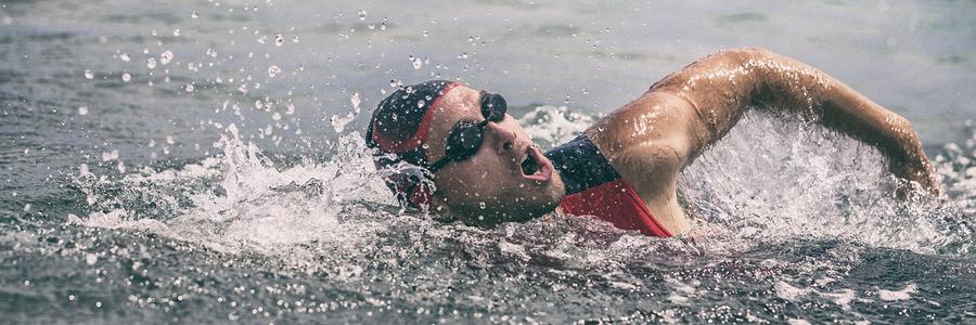 Swim triathlete man swimming freestyle crawl in ocean panorama b