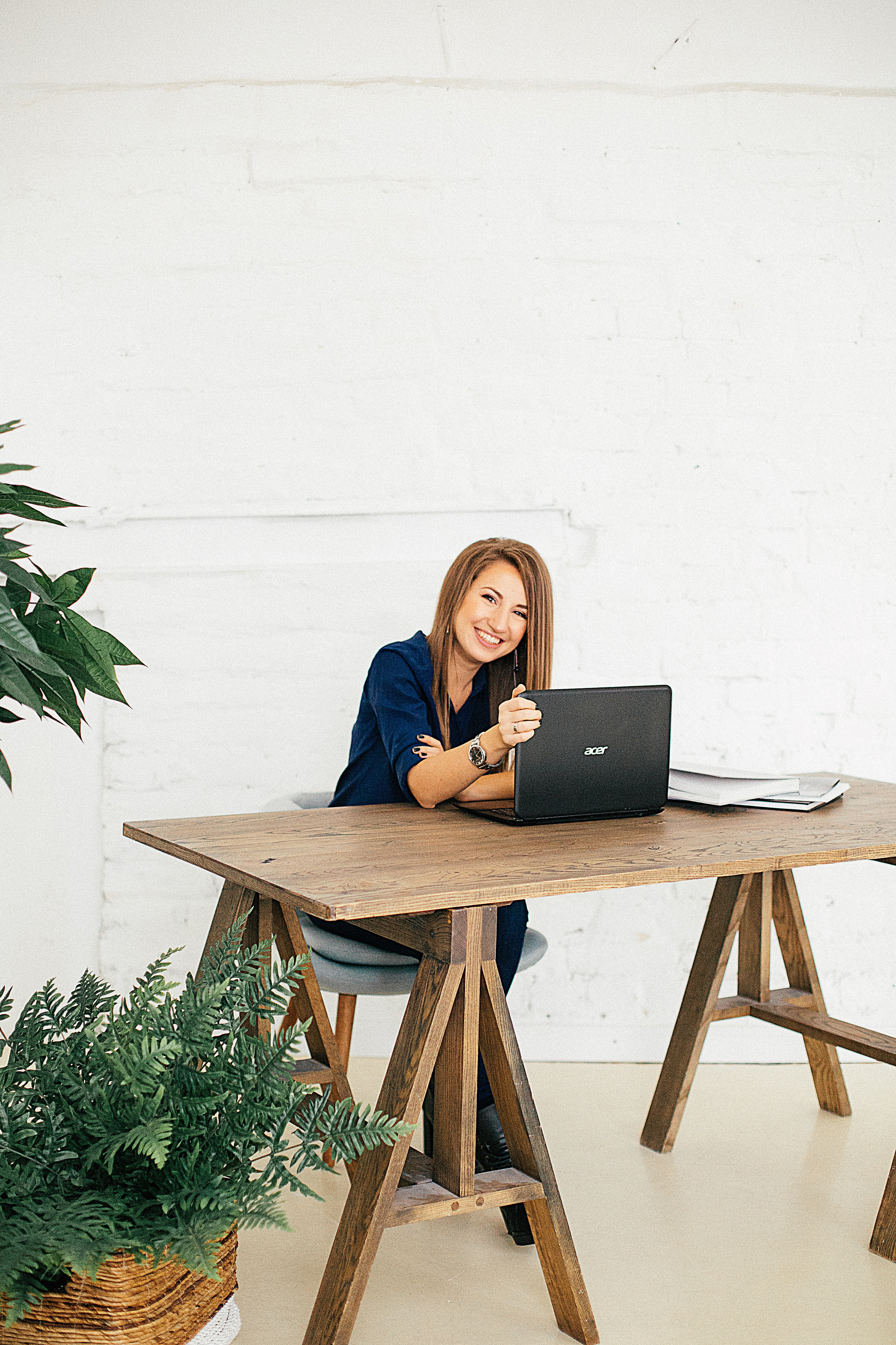 woman-in-wooden-table-using-computer-behind-white-wall-3681589